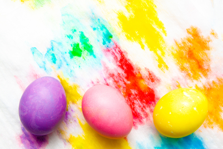 Colorful Easter eggs frame border on multicolor painted background. top view, copyspace.