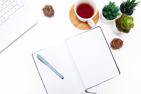 Workspace with laptop, notebook, sketchbook, succulent, cup of tea on white background. Flat lay, top view office table desk. Freelancer working place. copyspace.