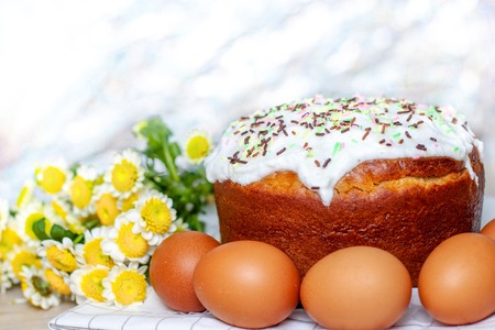 Easter cake and colored eggs yellow flower blossoms on background. Holiday food and easter concept. Selective focus. Copyspase.