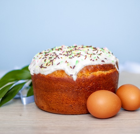 Easter cake and colored eggs on blue background. Holiday food and easter concept. Selective focus. Copyspase. Stock Photo