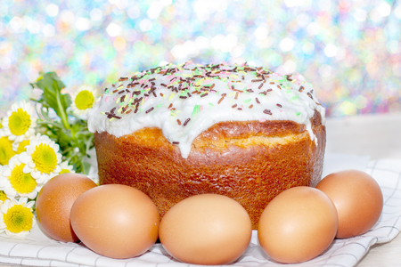 Easter cake and colored eggs yellow flower blossoms on background. Holiday food and easter concept. Selective focus.