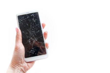 Mobile smartphone with broken glass screen in woman hand isolated on white. copyspace fo text. Service, repair and technology concept.