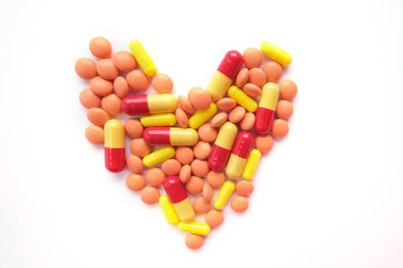 Heart made of multicolor tablets on white background. Epidemic, painkillers, healthcare, treatment pills and drug abuse concept. top view. flatlay.