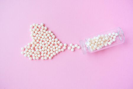 Heart made of homeopathic globules and glass bottle on pink background. Alternative Homeopathy medicine herbs, healtcare and pills concept. Flatlay. Top view. copyspace for text. Stok Fotoğraf