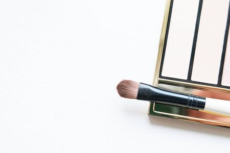Professional makeup tools eyeshadow palette and brushes on white background. Flat lay composition. magazines, social media. Top view. Copyspace.