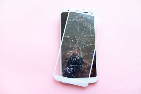 Mobile smartphone with broken glasstouch screen isolated on pink backgroung. copyspace fo text. Service, repair, technology and minimalism concept