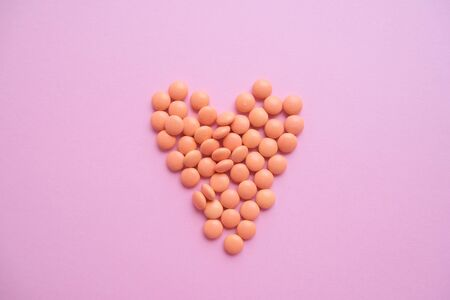 Heart made of orange tablets from glass bottle on pink background. copyspace for text. Epidemic, painkillers, healthcare, treatment pills and drug abuse concept. top view. flatlay.