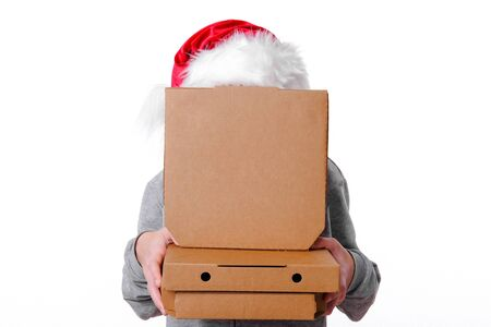 Christmas pizza and fastfood delivery. Unrecognizable man in santa hat hid behind pizza boxes in hands on white.