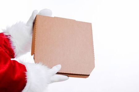 Christmas pizza and fastfood delivery. Santa Claus hands hold pizza box on white background. Mock up for text or logo.