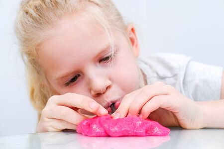 Blonde girl inflating bubble from pink glitter slime. Playing slime toy. Making slime at home.