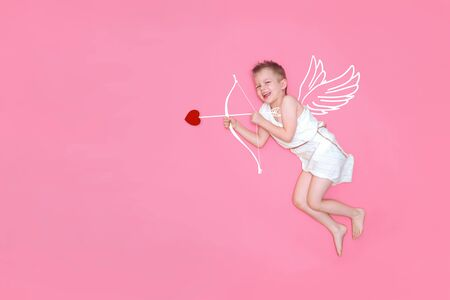 Happy smiling baby cupid in costume angel wings, bow and heart arrow isolated on pink studio background. Copyspace for text. Valentines day concept.