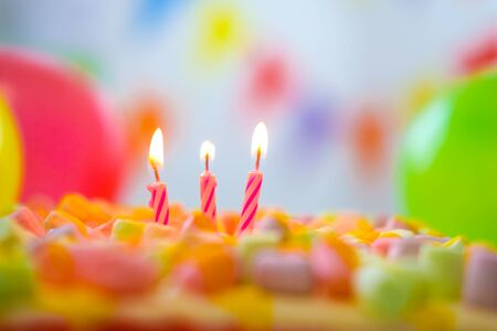 Festive colorful birthday card with three burning candles on rainbow cake and colorful balloons on background. Space for congratulatory text.