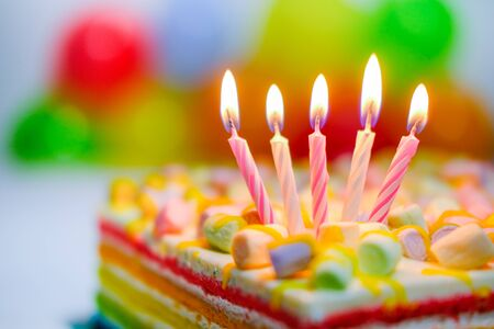 Festive colorful birthday card with five burning candles on rainbow cake and colorful balloons on background. Space for congratulatory text.
