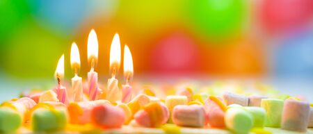 Festive colorful birthday banner with five burning candles on the cake and colorful balloons on background. Space for congratulatory text.