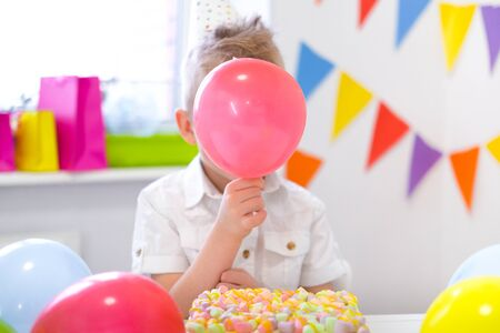 Blonde caucasian boy hid behind a red balloon near birthday rainbow cake. Festive colorful background. Funny birthday party.