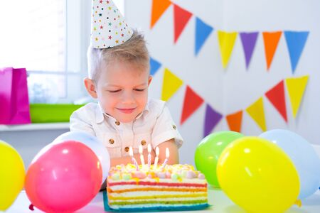 Blonde caucasian boy sits thoughtfully and dreamily at festive table near birthday rainbow cake and makes a wish. Colorful background with balloons.