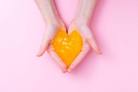 Orange slime in heart shape in kid hands. Girl hands playing slime toy on pink background. Making slime. Love and valentines day concept.
