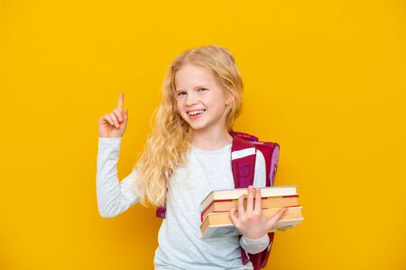 Back to school. Portrait of blonde school girl with bag and books. Pointing finger up. Yellow studio background. Education. smiling at camera Standard-Bild