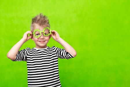 Little smiling caucasian boy in mask of leprechaun shamrock clover glasses for irish St. Patricks Day on green studio background. Copyspace.