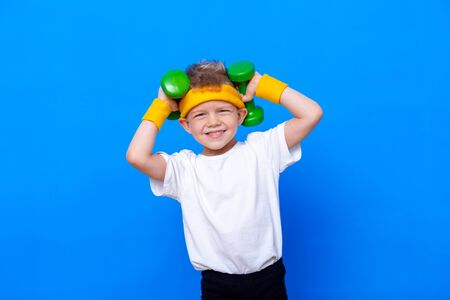 Fitness child. Portrait of sporty little boy with dumbbells over blue studio background. Gym workout. Child sportsman. Childhood activity. Sport. Fitness, health and energy. Success Stock Photo