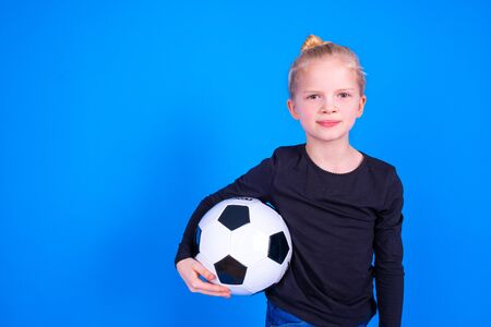 Soccer fans. Cute blonde girl in black shirt holding soccer ball in hands over blue studio background. Copyspace. Football game