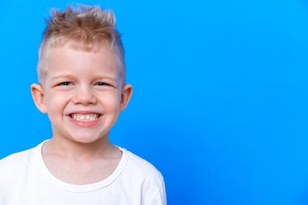 Portrait of happy child kid boy with wide smile on blue background. Health care, dental hygiene. Mockup, copy space