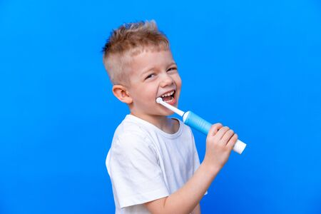 Happy child kid boy brushing teeth with electric toothbrush on blue background. Health care, dental hygiene. Mockup, copy space