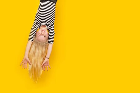 Excited crazy little blonde girl hanging happy upside down hands up over isolated yellow studio background. Emotion, expression. Copy space for text.