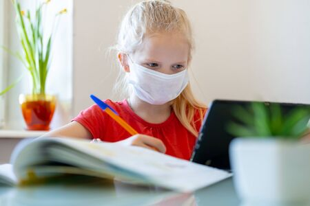 Distance learning online education. Sickness schoolgirl in medical mask studying at home with digital tablet in hand and doing school homework. coronavirus quarantine.