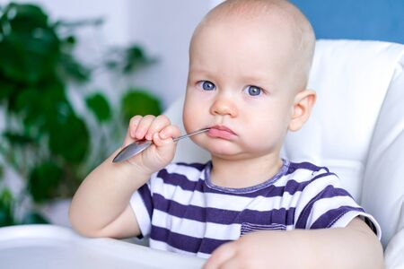 baby food. little serious caucasian child with spoon in his mouth on highchair. Newborn infant kids.