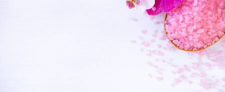 Banner Spa cosmetic and beauty treatment concept. Pink spa sea salt, white towel and purple orchid on white wooden background. copyspase flatlay.