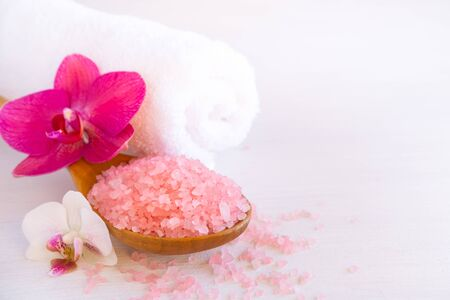 Spa cosmetic and beauty treatment concept. Pink spa sea salt, white towel and purple orchid on white wooden background. copyspase flatlay.