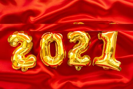 Foil balloons in the form of numbers 2021. New year celebration. Gold air balloons on red festive background. Holiday party decoration. top view