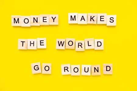 Sayings Money makes the world go round on yellow background