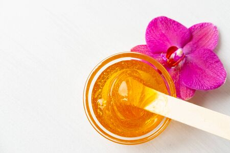 depilation and beauty concept - sugar paste or wax honey for hair removing with wooden waxing spatula sticks on flower background