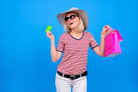 excited blonde caucasian girl in summer hat holding purple shopping bags and showing green credit mock up card, isolated on blue background. Copyspace. Summer shopping and sales concept. 版權商用圖片