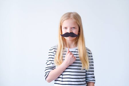 funny child blonde girl with mustache on grey background. Copyspace. Happy father day 版權商用圖片