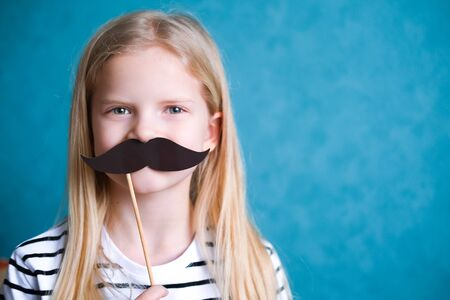 funny child blonde girl with mustache on blue background. Copyspace. Happy father day