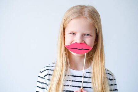 funny child blonde girl with red paper lips on grey background. Copyspace. Happy mother day. Birthday party 版權商用圖片