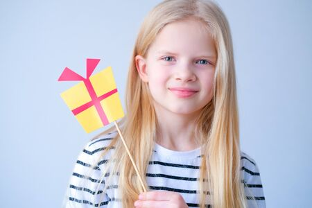 funny child blonde girl with yellow paper gift on stick on grey background. Happy Birthday party