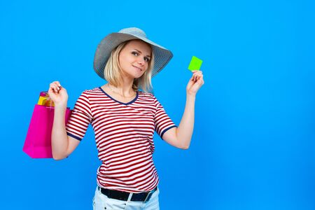 Summer shopping and sales. blonde caucasian girl in summer hat holding purple shopping bags and showing green credit mock up card, isolated on blue background. Copyspace