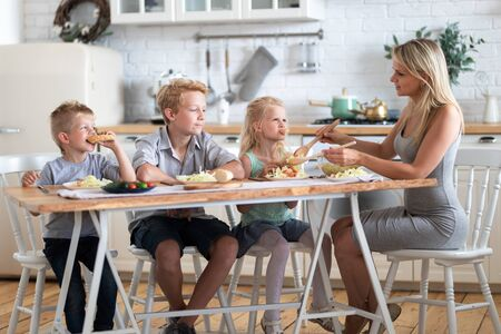 blonde family mother with three kids two sons and daughter eating healthy food in kitchen at home, mom puts green salad on plates to her kids. 版權商用圖片 - 148094857