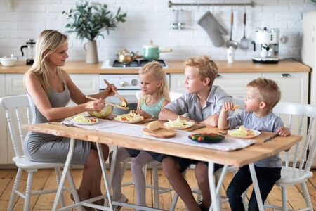 blonde family mother with three kids two sons and daughter eating healthy food in kitchen at home, mom puts green salad on plates to her kids. 版權商用圖片 - 148095342