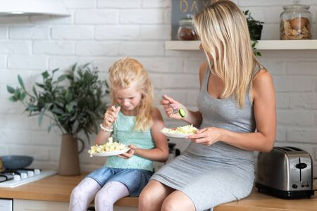 blonde family mother and daughter eating healthy food in kitchen at home, green salad on plates. 版權商用圖片