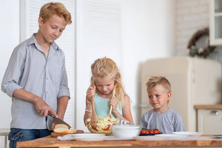 three blonde kids twoboys and girl on kitchen at home. Family prepearing healthy food , making green salad.
