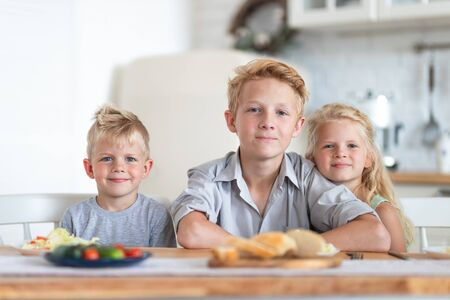 three blonde kids twoboys and girl on kitchen at home. Family eating healthy food , green salad on plates. Looking at camera. 版權商用圖片