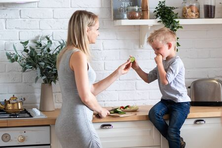 blonde family mother and son eating healthy food in kitchen at home, green salad on plates. 版權商用圖片