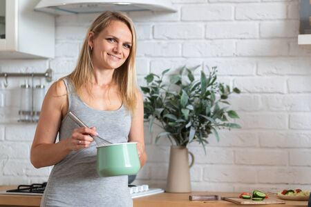 Portrait of cheerful woman cooking in kitchen at home. Blonde smiling caucasian girl looking at camera. Copyspace.