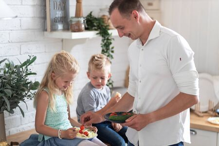 family father with three kids two sons and daughter eating healthy food in kitchen at home, dad puts green salad on plates to his kids. 版權商用圖片