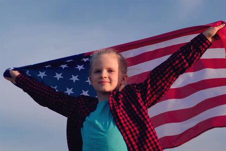 Blonde girl waving national USA flag outdoors over blue sky at summer - american flag, country, patriotism, independence day 4th july 版權商用圖片